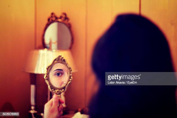 close-up of a beautiful young woman looking at mirror - hand mirror stock pictures, royalty-free photos & images