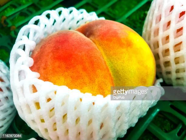 close-up of a big peach with white plastic mesh cushion - bare bum stock pictures, royalty-free photos & images