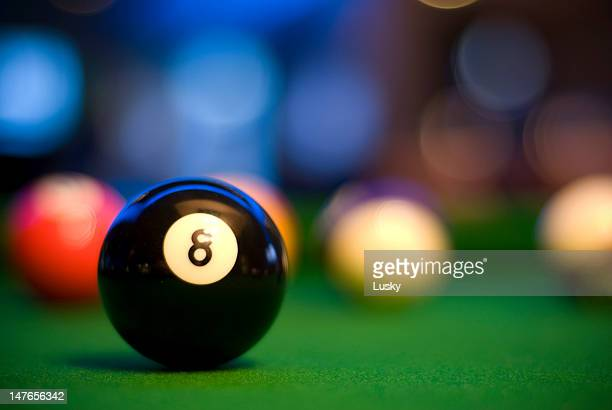 Close-up of a black 8 ball with blurred pool balls behind