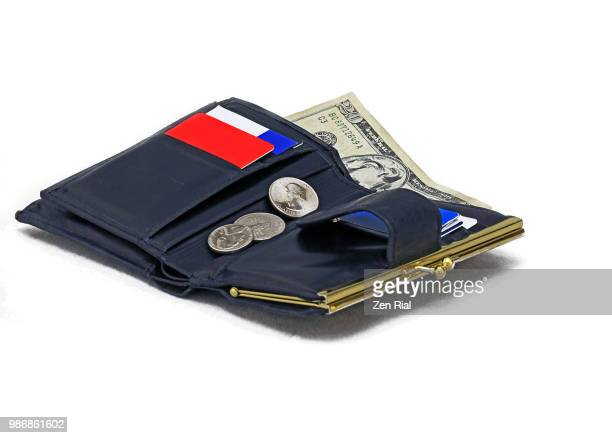 Close-up of a black ladies wallet on white background showing a twenty dollar bill and coins
