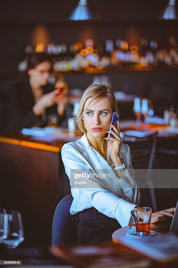 Nahaufnahme der blonden geschäftsfrau mit Handy und Laptop in ein Cafe / Restaurant : Stock-Foto