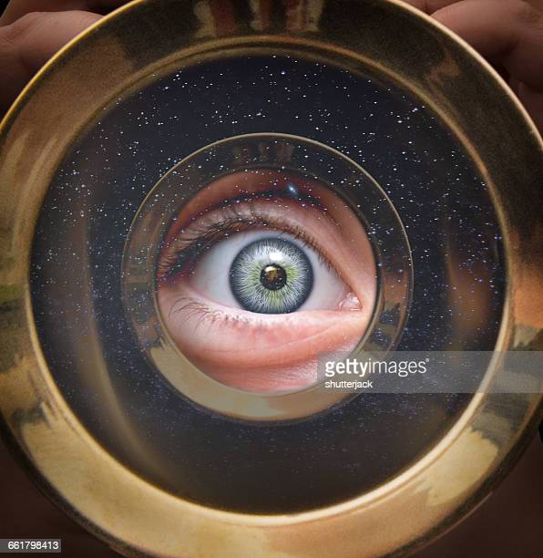 close-up of a blue eye looking through a telescope - telescope stock pictures, royalty-free photos & images