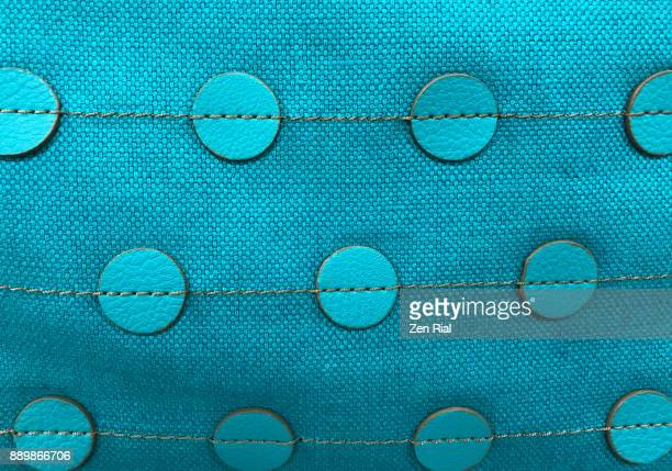 Close-up of a blue fabric with stitched circular pieces of leather