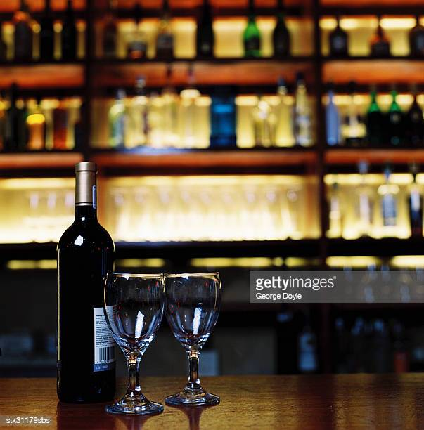 close-up of a bottle of wine with two wine glasses on a bar counter