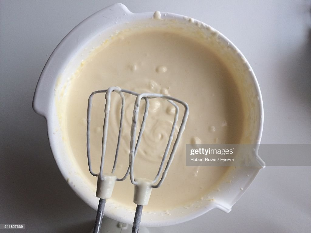 Close-up of a bowl of batter with hand mixer : Stock Photo
