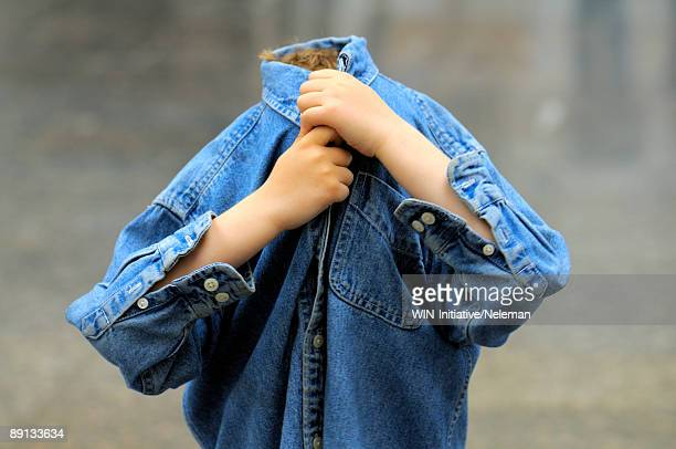 Close-up of a boy covering his face with his shirt, Kiev, Ukraine