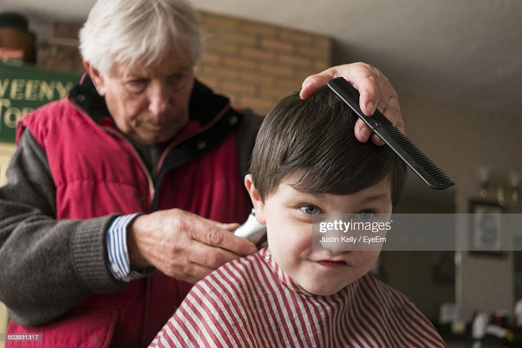 Close Up Of A Boy Getting Haircut At The Barber