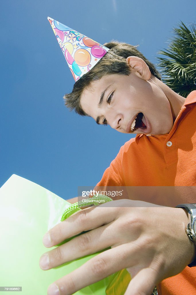 Close-up of a boy holding a gift bag : Stock Photo