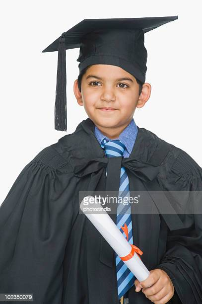 Close-up of a boy in graduation gown holding a diploma