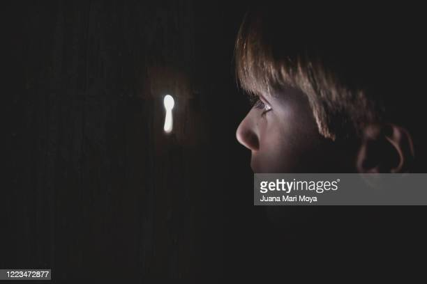 close-up of a boy looking through a keyhole.  idyllic, fairy-tale-like image - gossip stock pictures, royalty-free photos & images