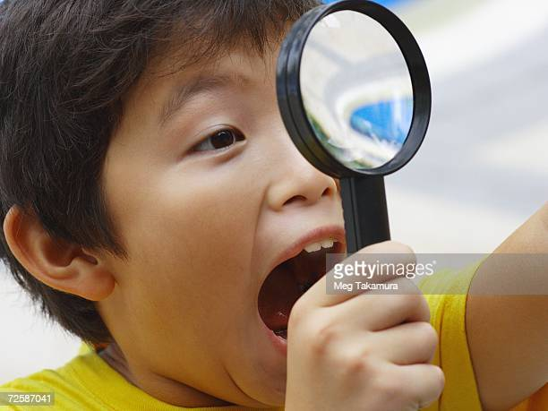 Close-up of a boy looking through a magnifying glass