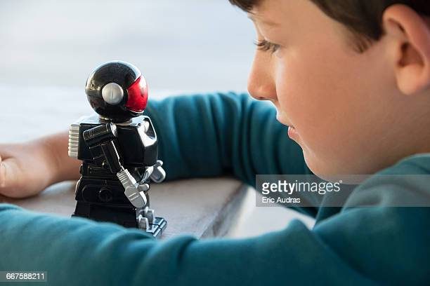 Close-up of a boy playing with toy robot