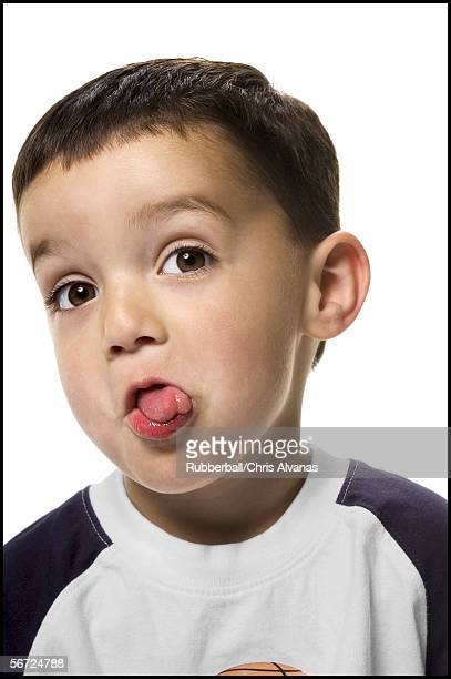 close-up of a boy sticking out his tongue - ugly kids stock photos and pictures