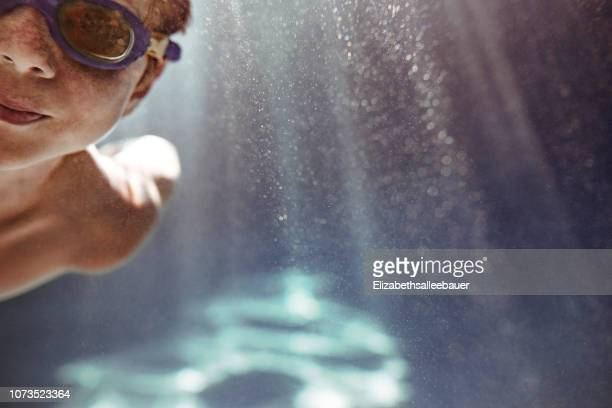 close-up of a boy swimming underwater in a swimming pool - 室内プール ストックフォトと画像