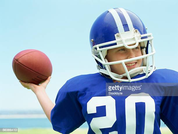 close-up of a boy wearing a helmet holding a football - american football uniform stock pictures, royalty-free photos & images