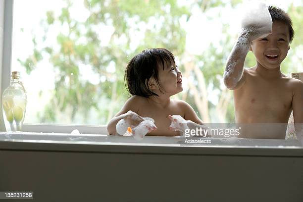 Close-up of a boy with and his sister playing with bubbles