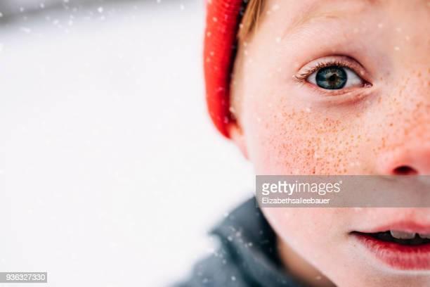 close-up of a boy with freckles standing in snow - surprise face kid - fotografias e filmes do acervo