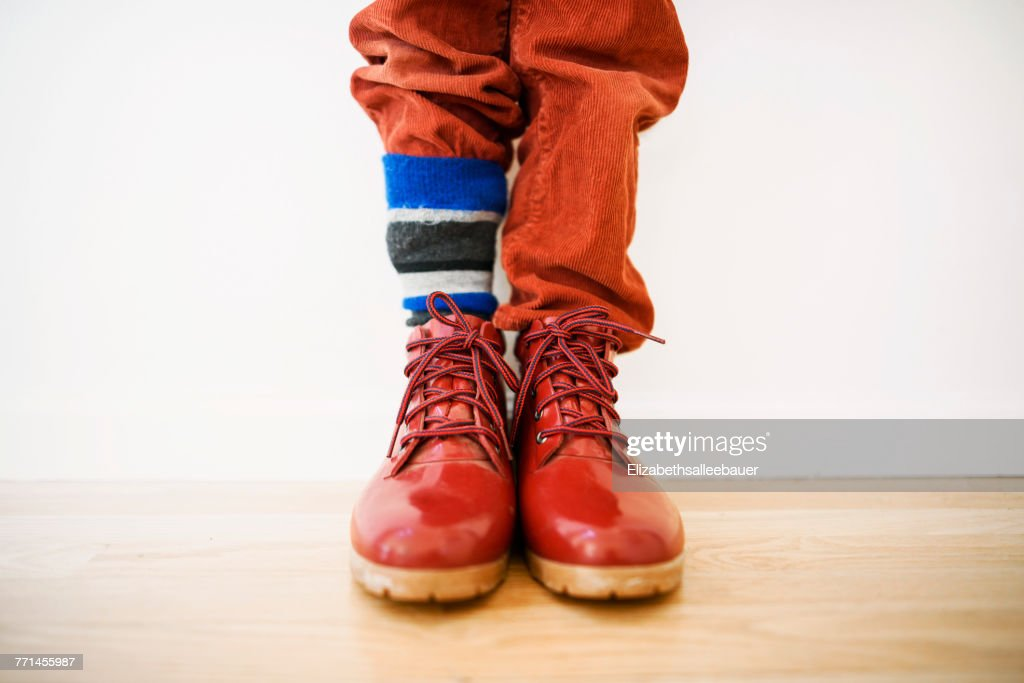 Close-up of a boy with his trousers tucked into one of his socks : Stock Photo