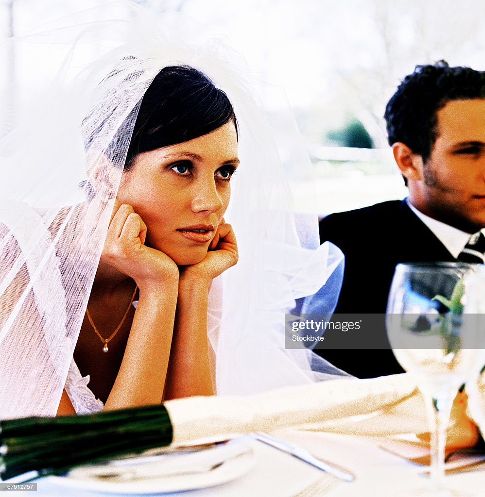 close-up of a bride sitting with elbows resting on a table : Stock Photo