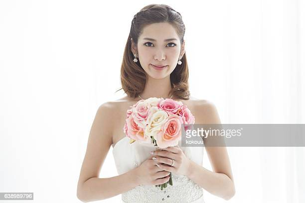 Close-up of a bride with a red bouquet.