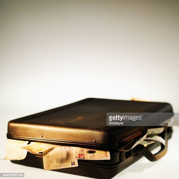 Close-up of a briefcase overflowing with U.K.. bank notes