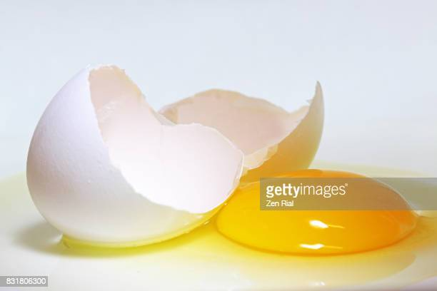 Close-up of a broken egg on white background
