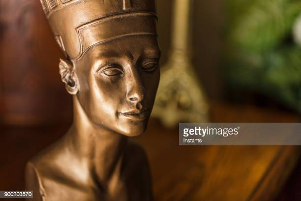 Close-up of a bronze colored Nefertiti bust, made with plaster.
