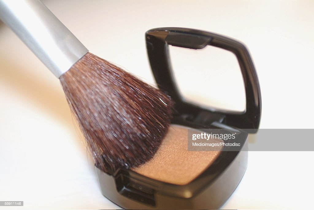 Close-up of a brush on an eyeshadow palette : Stock Photo