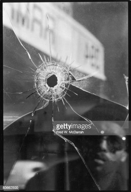 Closeup of a bullet hole in the window of the Ramrod bar as a man reflected in the glass looks in November 20 1980 The previous day the bar was the...