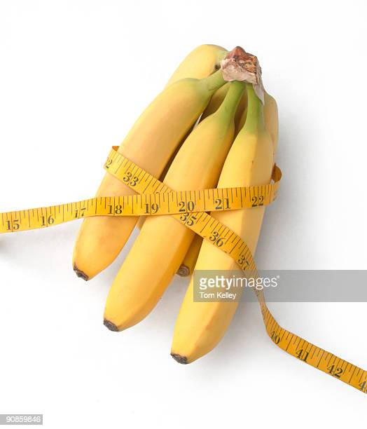 Closeup of a bunch of bananas wrapped in a tape measure and seen against a white background 2009
