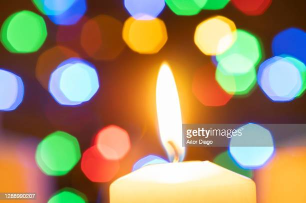 close-up of a burning candle with colourful lights in the background. - christianity stock pictures, royalty-free photos & images