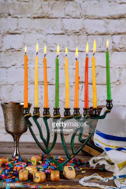 closeup of a burning chanukah candlestick with candles menorah - hannukkah stock pictures, royalty-free photos & images