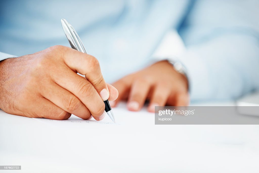 Close-up of a business man writing on paper : Stock Photo