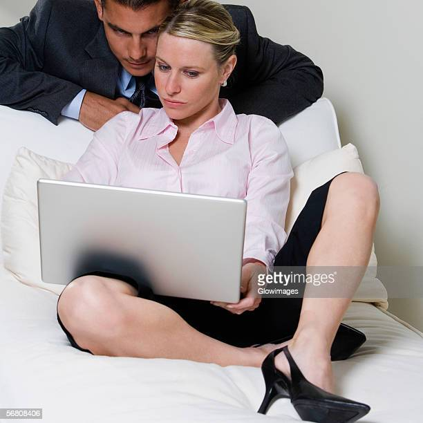 close-up of a businessman and a businesswoman looking at a laptop - bending over in skirt stock pictures, royalty-free photos & images