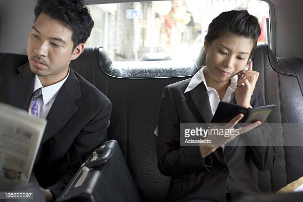 Close-up of a businessman and a businesswoman sitting in a taxi