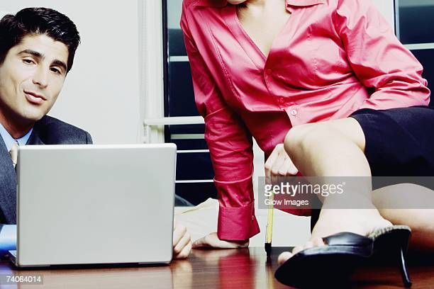Close-up of a businessman and a businesswoman sitting on a desk