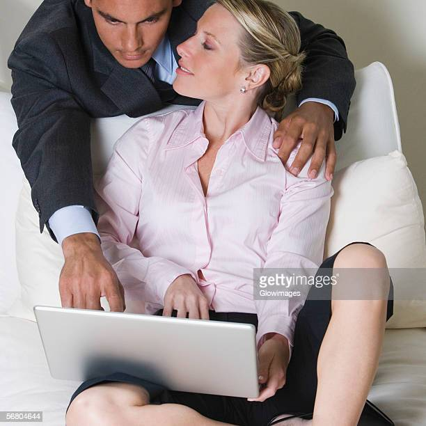 close-up of a businessman and a businesswoman using a laptop - bending over in skirt stock pictures, royalty-free photos & images