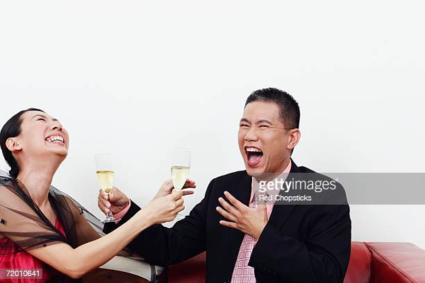 Close-up of a businessman and a mid adult woman holding glasses of champagne and laughing together