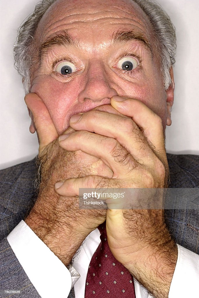 Close-up of a businessman covering his mouth in surprise as he looks at the viewer. : Stock Photo