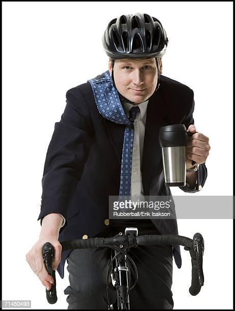 Close-up of a businessman cycling with a mug in his hand