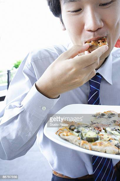 Close-up of a businessman eating a pizza