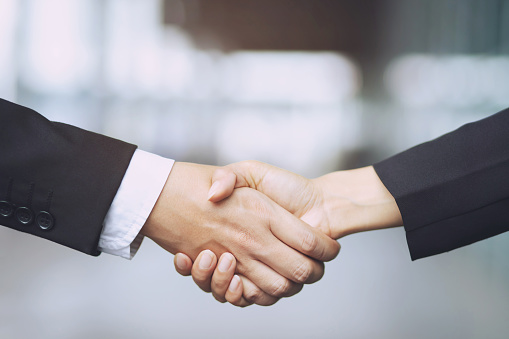 Closeup of a businessman hand shake businesswoman between two colleagues OK, succeed in business Holding hands. 1141688567