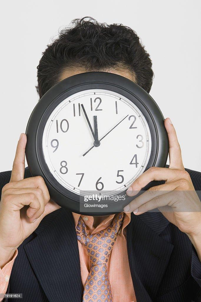 Close-up of a businessman hiding his face with a clock : Foto de stock