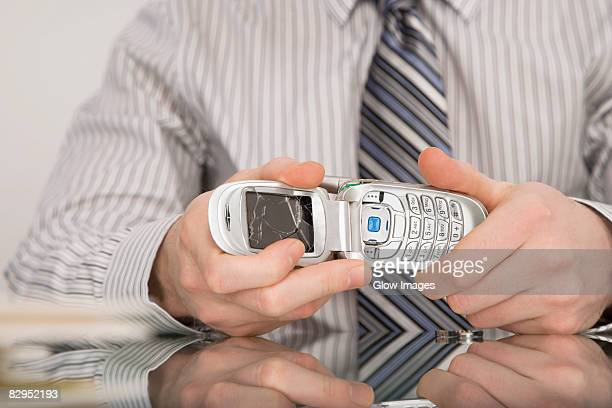 Close-up of a businessman holding a broken mobile phone