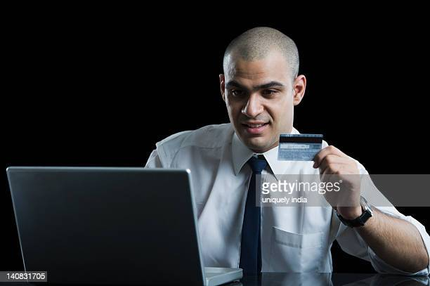 Close-up of a businessman holding a credit card and using a laptop