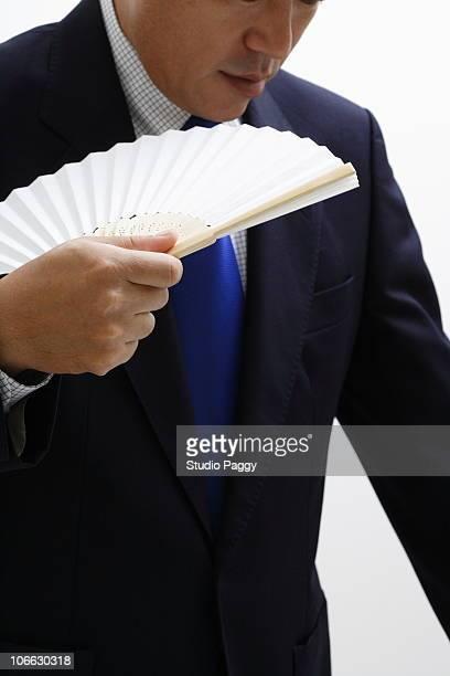 Close-up of a businessman holding a folding fan