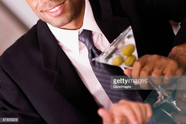 Close-up of a businessman holding a martini glass