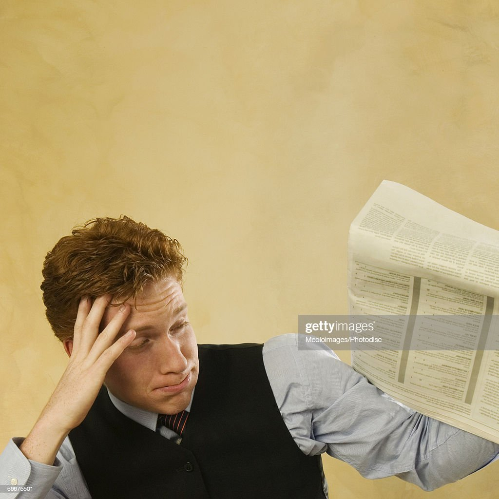Close-up of a businessman holding a newspaper : Stock Photo