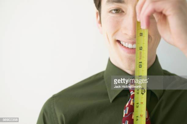 Close-up of a businessman holding a ruler in front of his face