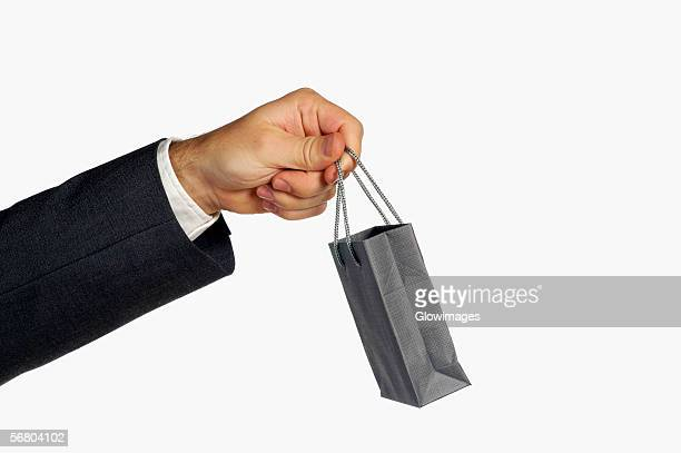 Close-up of a businessman holding a shopping bag